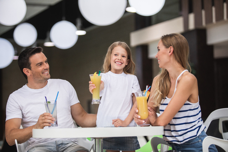Unforgettable time together. Waist up portrait of smiling kid holding glass of cocktail with joy. Mother and father are sitting nearby and looking at child with care and love while drinking