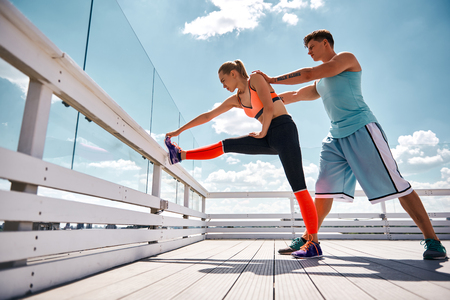 Athletic woman is warming-up by putting one leg on terrace fence and bending to it. Strong man is standing behind her and assisting by pushing her back. They are having joint workout on terrace high above city