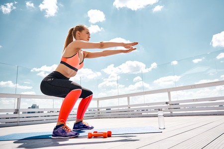 Sporty woman is doing squats on roof top of urban house. She is straightening arms forward and looking far away. Female is using also dumbbells and bottle of water for training in warm weather Stockfoto - 105484541