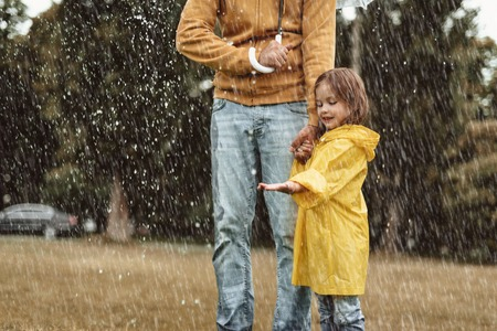 Full length side view of happy kid standing with father outside. She is stretching hand with content enjoying wet weather on nature with dad