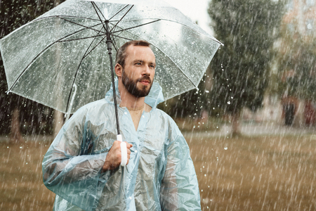 Waist up portrait of thoughtful male meditating outside. He is standing in park holding umbrella in hands looking distantly in considerations Stock Photo