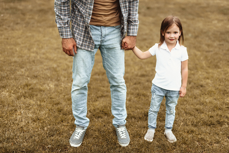 Full length portrait of little girl holding father hand outdoors. They are standing on grass together. Small kid is delighted and joyful 版權商用圖片