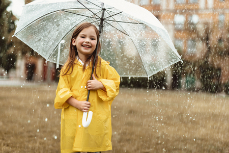 Waist up portrait of smiling child spending time outdoors. She is standing with umbrella in hands and laughing Stock Photo