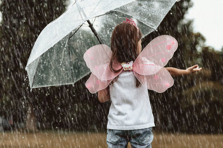 Little girl wearing fairy costume catching water drops with hands outside. She is standing with turned back and holding umbrella with content Stock Photo - 105520326