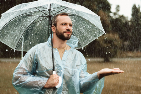 Waist up portrait of smiling male standing outside and holding umbrella. He is stretching hand in delight trying to catch water drops