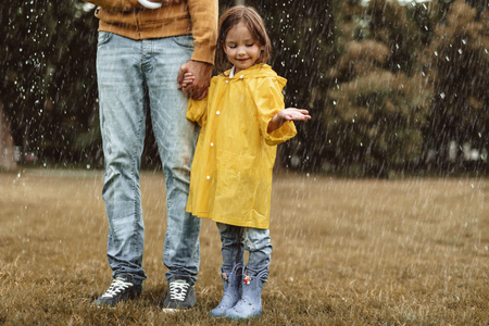 Full length of delighted kid catching water drops outside. She is standing and holding man hand with content