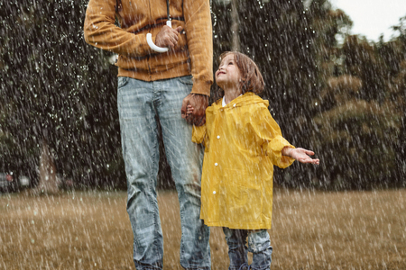 Side view of little girl smiling to father outside. They are walking in rain with umbrella. Happy child is looking upwards with content