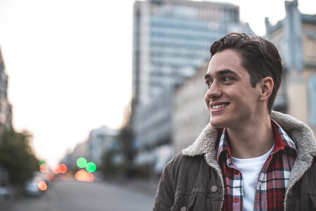 Side view of cheerful attractive man walking on street on his own.  He is looking sideways and smiling. Copy space in left side