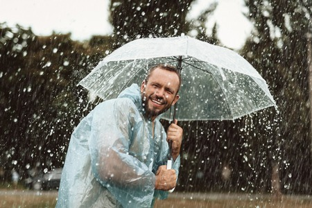 Waist up portrait of laughing man having fun outdoors. He is holding umbrella and feeling relaxed and pleased