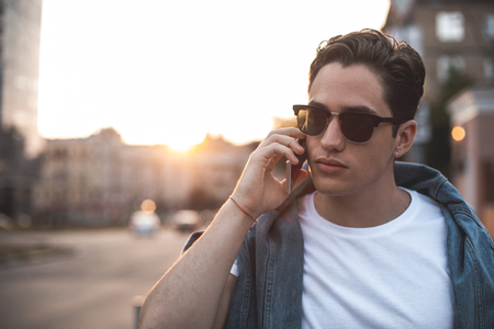 Waist up portrait of serious male wearing sunglasses and having conversation on phone. He is walking outside at sunset. Copy space in left side