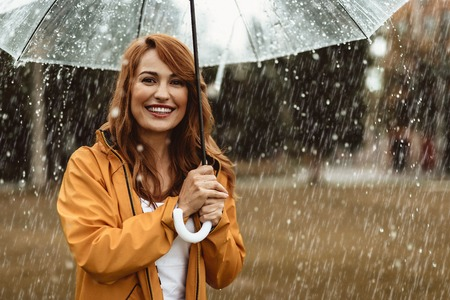 Waist up portrait of laughing pretty woman holding umbrella outdoors. She is looking at camera with sincere smile and delight. Copy space in right side