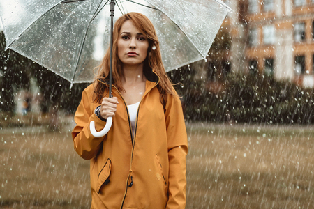 Waist up portrait of unhappy girl holding umbrella in hands. She is looking at camera with discontent