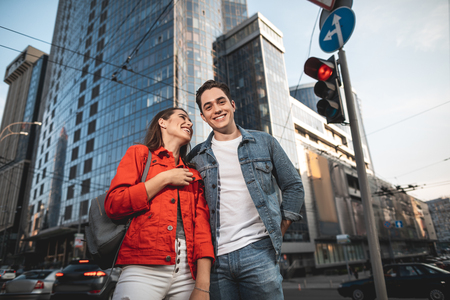Waist up portrait of joyful man standing near girlfriend and smiling. She is looking at him and laughing. They are content to walk on street 写真素材