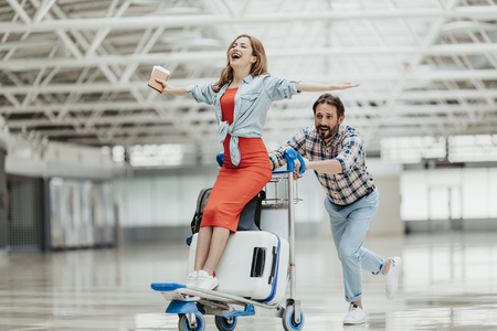 Full length portrait of beaming woman gesticulating hands while riding on luggage trolley. Laughing bearded male carrying her