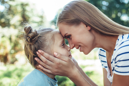 Profile of loving mom holding daughter cheek. Happy woman is looking at young child and smiling with delight. They are touching noses and foreheads with joy