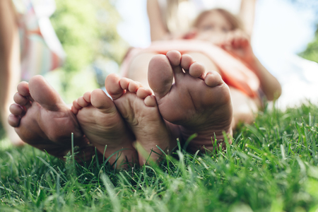 Low angle focus on female feet resting on grass. Happy mother and daughter enjoying time together on nature