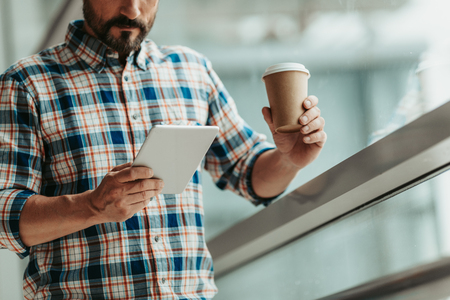 Orderly bearded man using contemporary digital device while drinking cup of coffee indoor