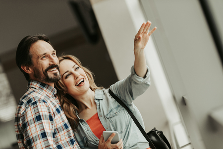 Portrait of happy bearded male hugging cheerful female. She gesticulating hand and holding mobile. Pleased couple during communication concept