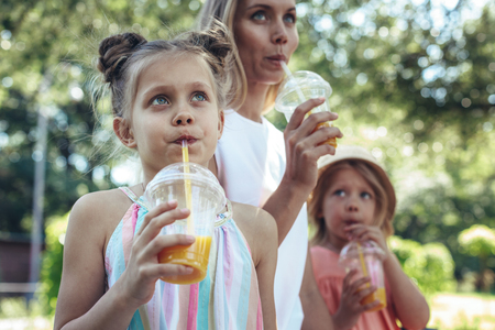 Waist up portrait of small girl sitting outside beside her mother and sister and sipping juice together. She is looking upwards with curiosity and interest
