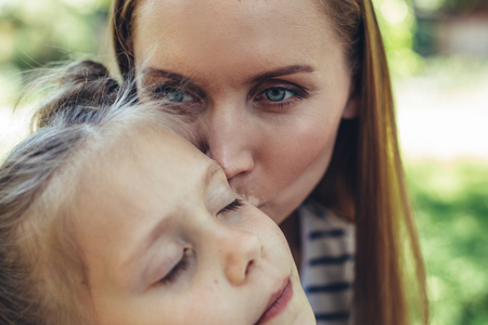 My sweetie. Delighted woman kissing daughter on cheek while hugging her. Small girl is bonding to mom with closed eyes