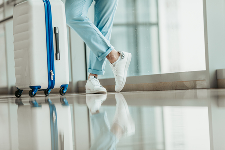 Close up man legs situating near big baggage. They reflecting on white clear floor