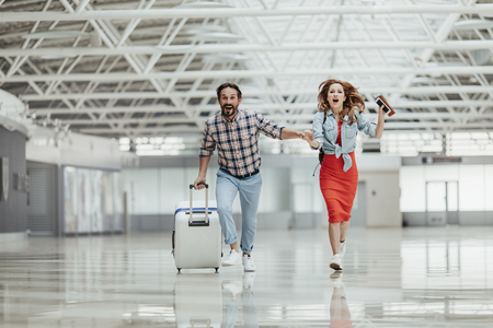 Ganzaufnahme eines lachenden bärtigen Mannes mit Koffer und abgehendem Mädchen mit Dokumenten und Telefon in der Hand, die sich am Flughafen beeilen Standard-Bild