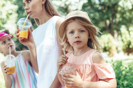 Focus on little kid sitting outside and holding plastic cup in hands. Mother and sister are beside. They are enjoying beautiful weather together