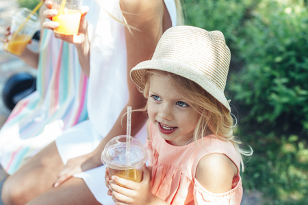 Waist up portrait of smiling small child sitting in park with mom and sister and holding plastic cups. She is enjoying summer time with joy Banco de Imagens