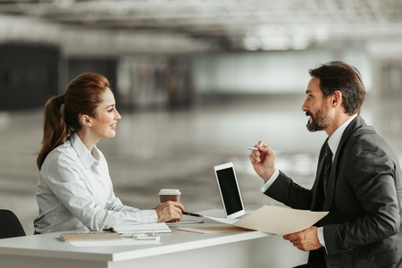 Side view beaming girl talking with outgoing bearded businessman. He gesticulating hands and keeping folder with information. They sitting at desk Imagens