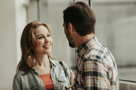 Outgoing girl with attractive smile speaking with man indoor. Glad communication concept Banque d'images