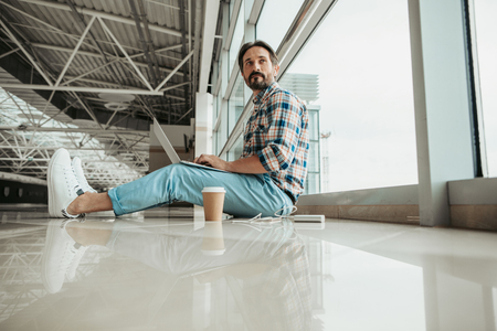 Low angle portrait of pensive unshaven man using laptop while locating indoor Standard-Bild