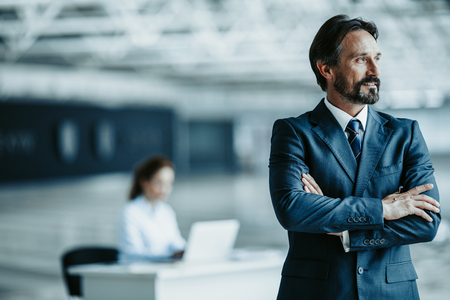 Portrait of bearded happy businessman with crossing hands situating in modern office. Secretary working at table behind him