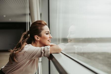Vue de côté femme heureuse rêvant tout en regardant la fenêtre à l'intérieur. Elle se repose pendant le travail