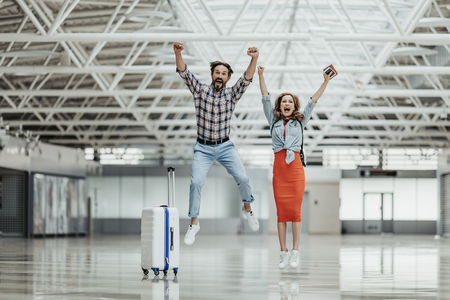 Full length portrait of cheerful unshaven male and positive female jumping while expressing happiness. They situating near luggage at airport. Beginning of journey concept