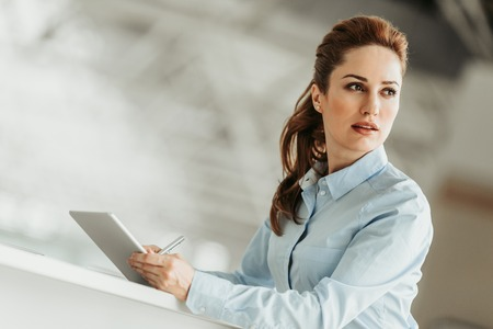 Portrait of concentrated businesswoman typing in electronic tablet while looking away