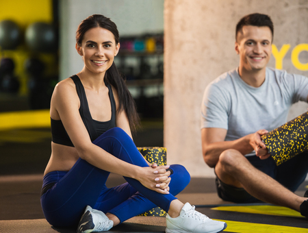 Focus on smiling lady sitting on floor during training in sport studio. Positive man is having good time while being near her and holding outfit. They are having workout indoors with foam rollers
