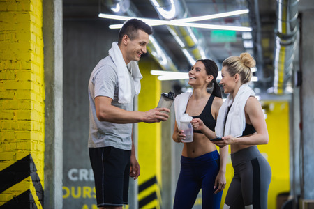 Two smiling ladies are chatting with their male mate in fitness studio. They are sharing experience while quenching thirst after training. Sportspeople are holding water flasks and using towels while standing 版權商用圖片