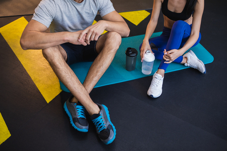 Top view of man and woman relaxing together after training indoors. They are sitting on floor and having water from sport flasks. Both of them are wearing sports clothes and sneakers