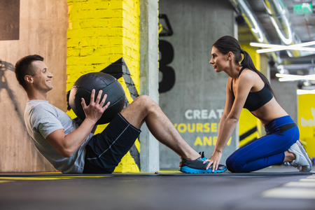 Athletic lady is helping man exercising by holding his feet. Happy man is training abdominal muscles by lifting body while using med ball. Motivation concept