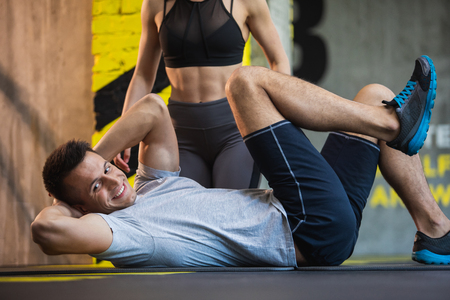 Cheerful fit guy is exercising obliques on mat in fitness studio. Ripped woman is kneeling behind him. Workout for health and beauty concept