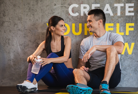 Positive guy is coGrinning couple is relaxing and sitting on floor in sport center after workout. They are having pleasure while chatting and resting. Woman is holding flask with water for quenching thirstmmunicating with girlfriend in gym