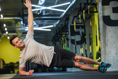 Cheerful man is exercising obliques un sport club. He is planking while balancing on elbow and lifting up one arm. Training with pleasure concept Reklamní fotografie