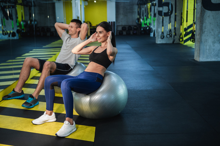 Happy man and woman are training abdominal muscles in fitness studio. They are sitting on balls and balancing on them for stronger effort. Copy space in right side