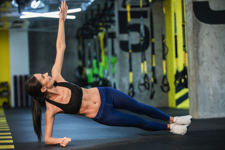 Happy lady is exercising obliques in static position in fitness studio. She is balancing on one elbow and raising other arm while looking at it. Athlete is training both strength and flexibility Stock Photo