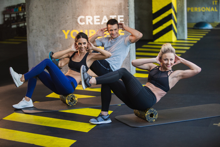 Joyful two fit ladies and guy are exercising together in fitness studio. They are doing abdominal crunches on foam rollers synchronously. Exercising with friends concept