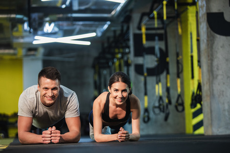 Merry man and woman are doing plank simultaneously in sport studio. They are balancing on elbows and looking at camera. Male and female are straining all body while exercising core Stock Photo