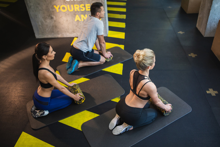 Top view of two slender women and shredded man having joint workout in sport club. They are kneeling on mat and leaning on foam rollers. Training with equipment together concept