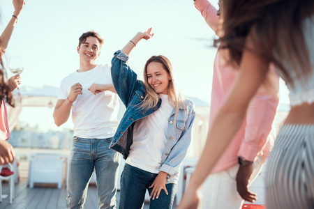 Pleased lady flourishing arm while dancing with outgoing men and female comrades outside