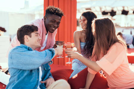 Outgoing girls and beaming men tasting delicious beverage while speaking together. Happy friends during leisure concept