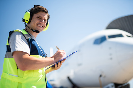 Looking positive. Aviation technician looking at camera with smile and writing information on clipboard. Passenger airplane on blurred background Stock Photo